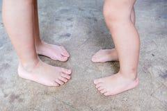 Oigenkännliga barfota barn med smutsig fot som står på konkret golv/armodbegrepp royaltyfri foto