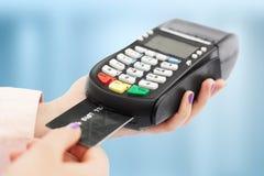 Oigenkännliga kvinnahåll som nallar maskinen och kreditkorten, löner för köp, bruk packar ihop terminalen shoppar in, isolerat öv arkivfoton