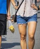 Oigenkännliga par på bönder marknadsför - mannen och kvinnan i kortslutningar som bär en påse av squash, blomstrar royaltyfri foto