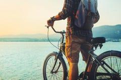 Oigenkännligt handelsresandemananseende med cykeln på kust och tycka omsikt av resande avkoppling för natursolnedgångsemester som Arkivbild