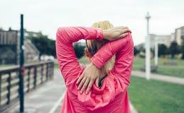 Oigenkännlig kvinna som sträcker armar, innan utbildning utomhus Royaltyfri Foto