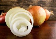 Oignon et anneaux d'oignon frais sur le fond en bois Image libre de droits