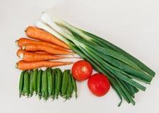 Oignon frais vert, tomate rouge, carotte et pois sur le blanc en bois Image libre de droits