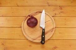Oignon rouge avec un couteau sur un hachoir Image stock