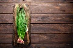 Oignon vert ou oignon blanc sur le panneau en bois, ciboulette fraîche de ressort Photographie stock libre de droits