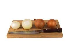 Oignons coupés en tranches frais sur un conseil sur un fond blanc Photographie stock