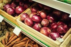 Oignons et carottes sur l'étagère de légume de supermarché photos stock