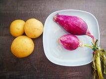 Oignons et pommes de terre italiens sur une maquette en céramique bleue de plat Image libre de droits