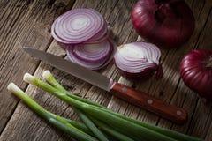 Oignons frais assortis de ferme sur une table en bois aux oignons de ressort Image libre de droits