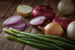 Oignons frais assortis de ferme sur une table en bois aux oignons de ressort Photo stock