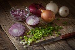 Oignons frais assortis de ferme sur une table en bois aux oignons de ressort Photos libres de droits