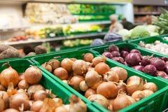 Oignons sur l'étagère de légume de supermarché Photos libres de droits