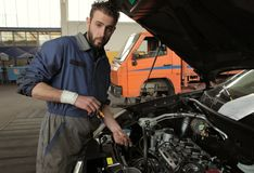 Oil. Auto mechanic chaking oil engine Royalty Free Stock Photo