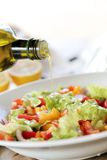 Oil is added into a salad. Olive oil is being added into a vegetable salad stock photos