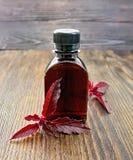 Oil with amaranth on dark board Stock Photo
