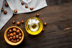 Oil as cosmetics. Haselnut oil near nut in shell on dark wooden background top view copyspace. Oil as cosmetics. Haselnut oil near nut in shell on dark wooden Stock Image