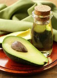 Oil of avocado and fresh fruit. On wooden table Royalty Free Stock Photography