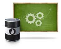 Oil barrel with gear icons on blackboard with Royalty Free Stock Image
