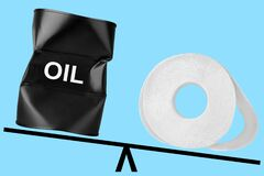 Oil barrel and toilet paper on scales, oil drum and bog roll balance, oil price drop concept, low cost barrel banner, fuel value