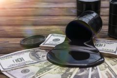 Oil against the background of dollar bills. fuel industry. Oil barrels and poured money dollar currency. bargaining. Exchange. oil business. Profit income Stock Photo