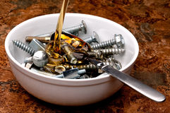 Oil being poured onto a bowl of nuts and bolts Stock Image
