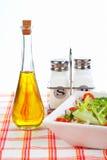 Oil bottle, green salad, salt and pepper Stock Image