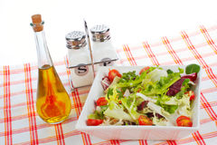 Oil bottle, green salad, salt and pepper Royalty Free Stock Photography