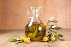 Oil bottle and olive branch. On wood royalty free stock photo