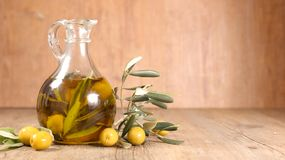 Oil bottle and olive branch. On wood royalty free stock image