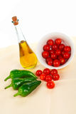 Oil bottle, red tomatos cherry and green pepper Stock Images