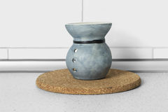 Oil burner. Blue ceramic oil burner on a table as a background royalty free stock images
