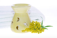 Oil burner yellow flower and white towel Stock Photos