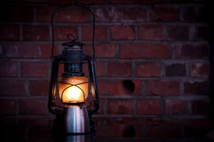 Oil burning storm lantern. A traditional oil burning storm lamp or lantern positioned on a table against a red brick background Royalty Free Stock Images