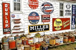 Oil cans and metal signs. ROLLAG, MINNESOTA, Sept 1. 2016: Oil cans and metal advertising signs of oil companies are displayed on an old filling station wall at Stock Images