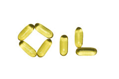 Oil capsules. Spelling the word oil against white background Royalty Free Stock Photography