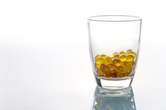 Oil capsules in glass on white background  with copy space..jpg Royalty Free Stock Photo