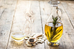 Oil in carafe with pepitas and rosemary on wooden background mock-up. Extra oil in carafe with pepitas and fresh rosemary on wooden desk background mock-up Stock Photography