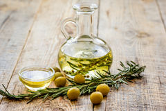 Oil in carafe with spices and olive on wooden background mock-up. Extra oil in carafe with spices and fresh olive on wooden desk background mock-up Royalty Free Stock Image