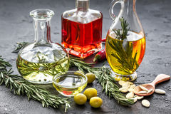 Oil in carafe with spices, olives and chili on stone background. Extra oil in carafe with spices, green olives and fresh chili on stone desk background Stock Images