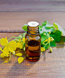 Oil with celandine on dark board stock images