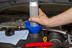 Oil Change. One liter oil container, tools, hand and car engine Royalty Free Stock Image