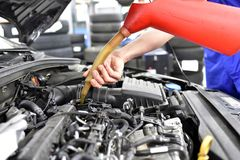 oil change from the engine of a car in a workshop by a professional mechanic - after-sales service stock images