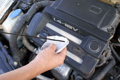 Oil check. Hand checking car engine oil Royalty Free Stock Photos