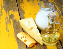 Oil and cheese on wooden board. Royalty Free Stock Images
