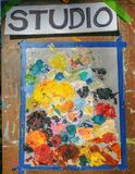 Oil Color Paint Studio Sign. With the paint palate with lots of colors, such as red, orange, yellow, green, blue, pink and black on it royalty free stock image