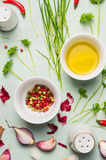Oil, colorful pepper in white bowls with fresh herbs and spices for cooking Royalty Free Stock Photo