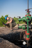 Oil company worker on the well. Oil company worker in a protective suit of wells Royalty Free Stock Photo