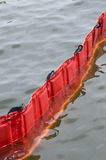 Oil containment boom. Closeup of red oil containment boom floating in water stock photography