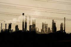 Oil crude refinery against the sunlight Stock Photos