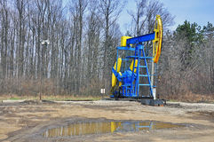 Oil derrick. Colored oil derrick near the forest stock image